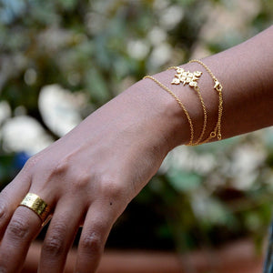 A Model's Hand Wearing Yenaé 14K Gold Plated Lalibela Cross Necklace As Bracelet