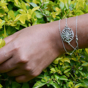 A Model's Hand Wearing Yenaé Rhodium Plated Axum Cross Necklace As Bracelet