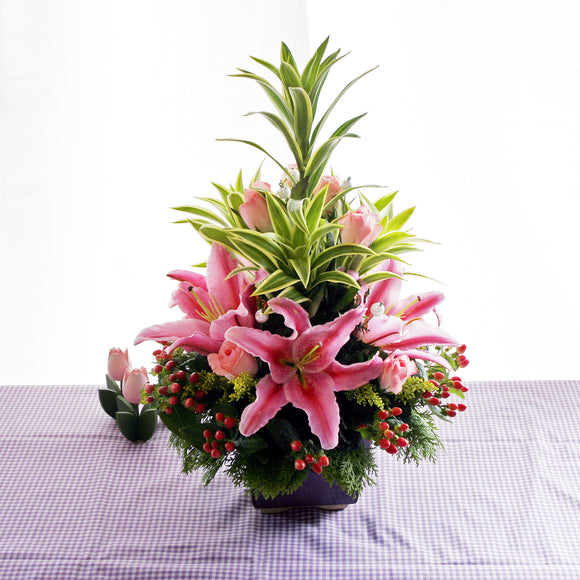 pink lilies, pink roses and red hypericum berries table flower arrangement