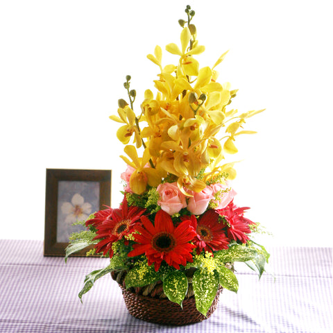 Yellow orchid table flower arrangement with red gerbera daisies and pink rose