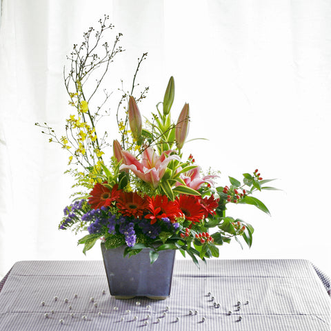 Table flower arrangement of pink lilies, red gerberas, red hypericum berries and yellow dancing orchids by Katong Flower Shop for Singapore Delivery