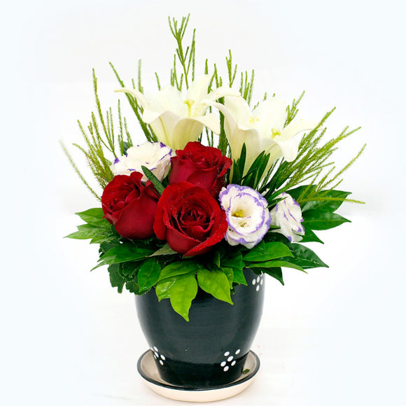 Floral arrangement with red roses, white lilies and eustomas in a vase.