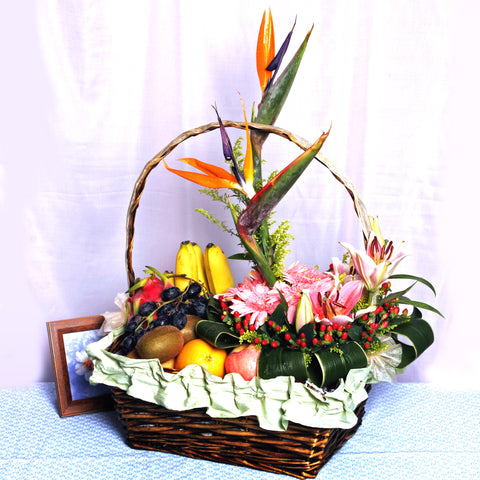 Fruit basket arranged with exotic bird's of paradise, pink gerberas, pink lilies and hypericums by Katong Flower Shop for Singapore Free delivery