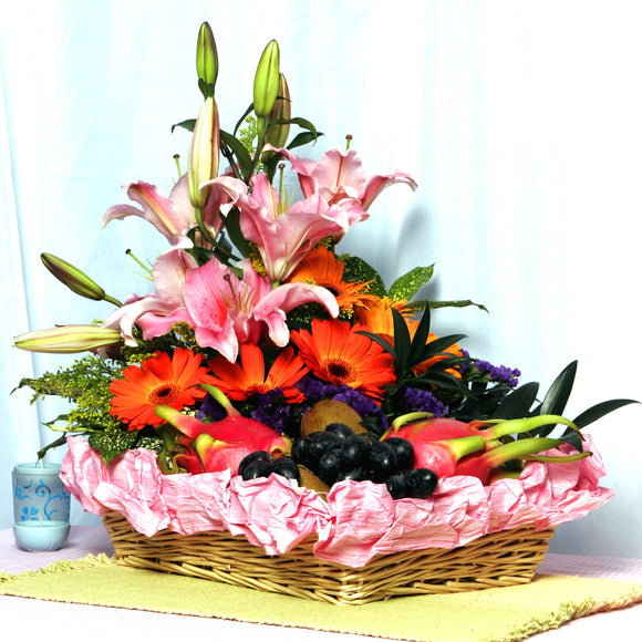 Bright and cheery fruit basket arranged with pink lilies and orange gerberas by Katong Flower Shop for singapore Delivery Options_Free Delivery