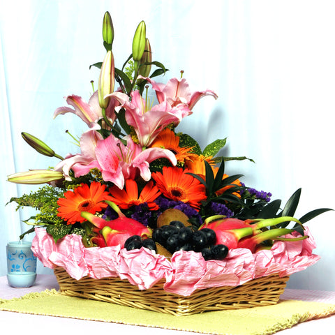 Bright and cheery fruit basket arranged with pink lilies and orange gerberas by Katong Flower Shop for singapore free delivery