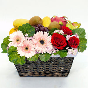 Get Well basket with tropical fruits and gerbera daisies, roses and green foliage by Katong Flower Shop for Singapore Delivery