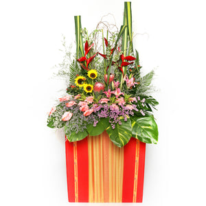 Gerbera daisies, lilies, sunflowers, heliconia and filler flowers arranged on a box stand for grand opening and congratulatory occasions by Katong Flower Shop for Singapore Delivery.
