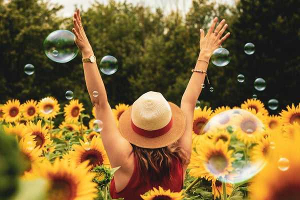 A happy, care-free woman raising her hands in a field of yellow sunflowers and bubbles