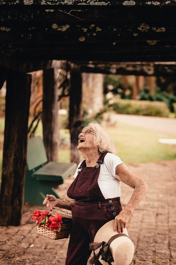 A happy grandmother on the sidewalk with a flower basket