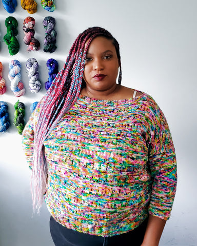 Woman with long braids in handknit multicolored sweater.