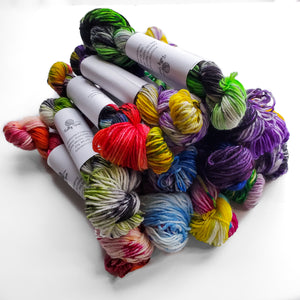 A stack of the mini skeins included in the set, one for each colorway of the Pride Collection.