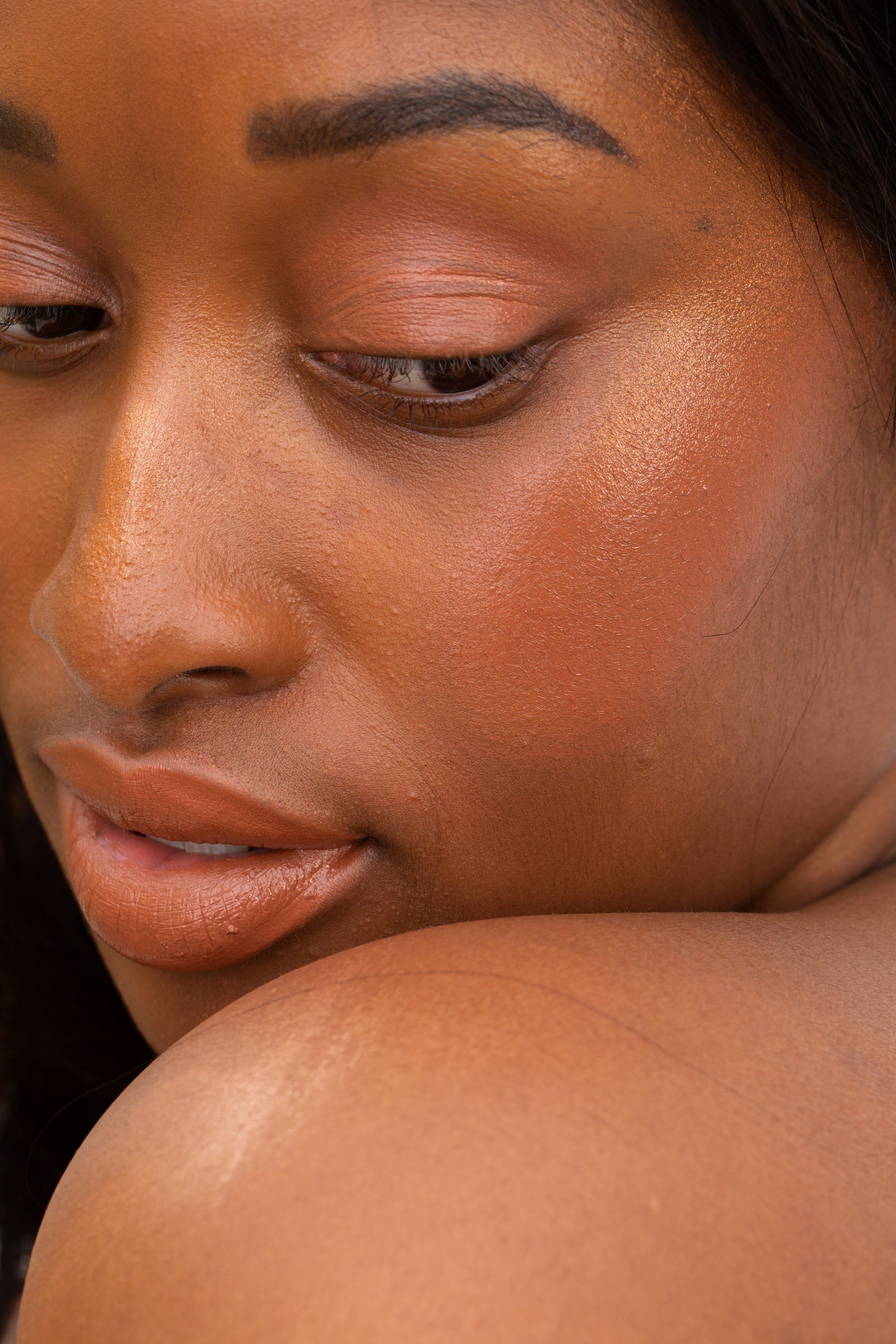 swatch of skin dew in cognac on cheekbones of deep complexion