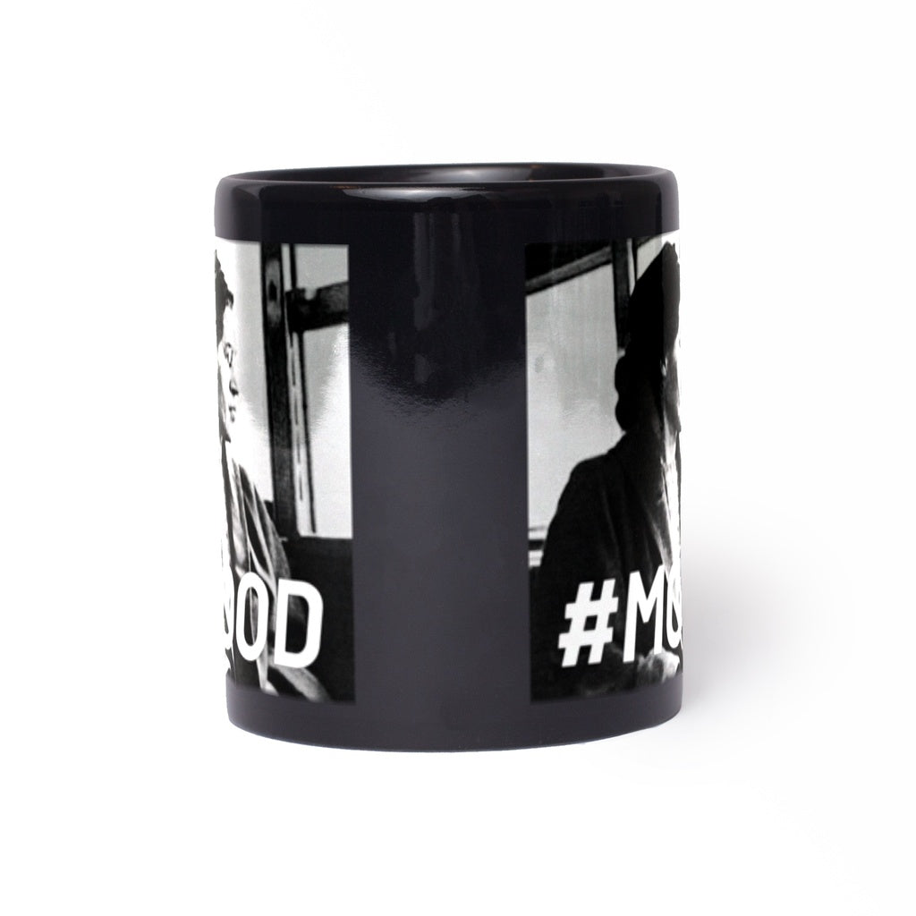 Lady sitting looking out of the window on a black 11ox mug with the hash tag Mood on it