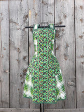Load image into Gallery viewer, An apron mde from  vintage pattern with prints of green shamrocks on a black background plus green plaid.