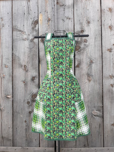 An apron mde from  vintage pattern with prints of green shamrocks on a black background plus green plaid.