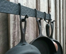 "Load image into Gallery viewer, Side view of 48"" hammer finish pot rack with the upgraded scroll end hooks shown.  Hooks are shown holding cast iron pans and a copper bottom skillet.  Mounted on a barn wood wall."