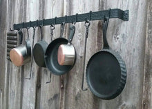 "Load image into Gallery viewer, Hand forged hammer finish pot rack made by a blacksmith.  48"" long, made of 2"" wide steel.has 10 movable hooks.  shown holding cast iron pans and stainless steel pots."