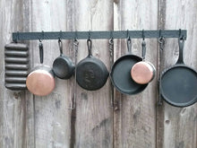 "Load image into Gallery viewer, Front view of 48"" hand forged hammer finish pot rack.  Made by a blacksmith.  Shown mounted onto a barn wood wall with cast iron pans, copper bottom pots and hand forged steak turners."