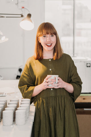 A picture of Cedar's founder, Lizzy in her studio in Manchester. With some Halcyon candle countainers waiting to be hand poured.