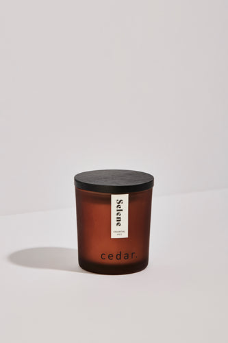 Small Selene essential oil candle in an frosted amber jar with a black wooden lid.