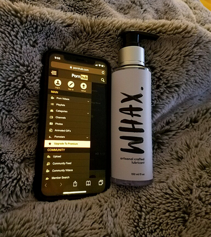 A phone showing Pornhub sits next to our masturbation lubricant