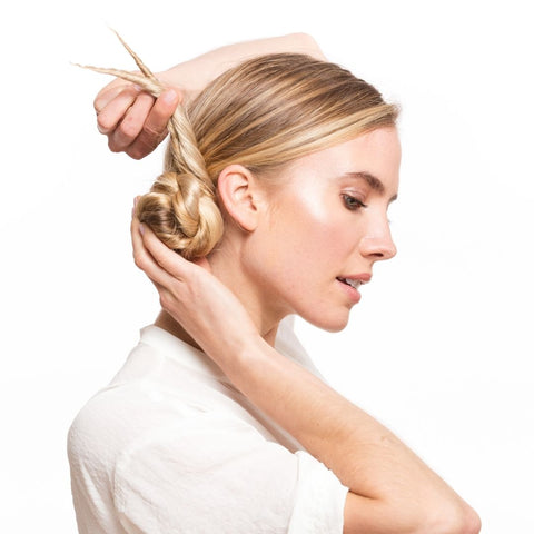 Blonde model doing her hair by wrapping her ponytail around a bun using Easy Updo Extensions