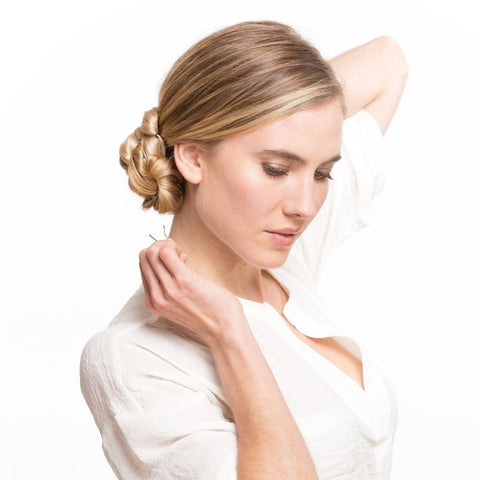 Blonde haired model using bobby pins to secure her updo hairstyle wearing a white shirt using Easy Updo Extensions