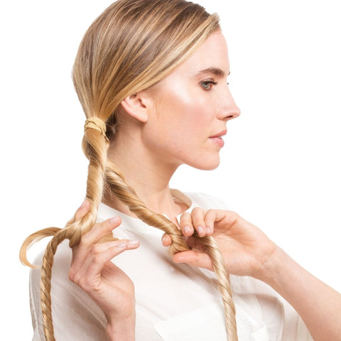 Model separating hair into 2 sections using Easy Updo extensions with white background doing her hair