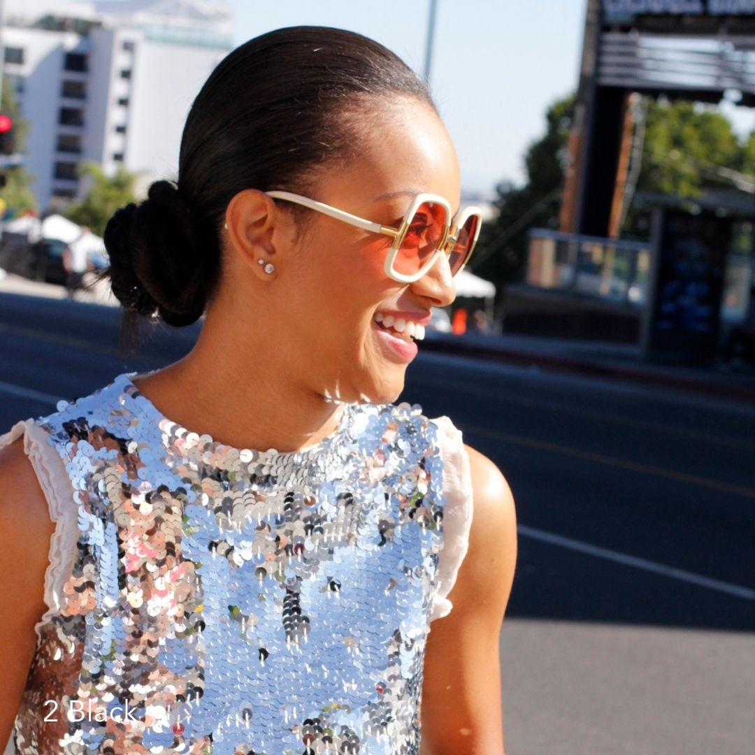 African American woman walking down street in sequin dress wearing bun and sunglasses