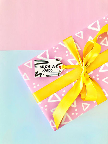 Pink geometric gift wrap by coconutacha, tied with gold ribbon and a black and white gift tag saying 'such a boss'