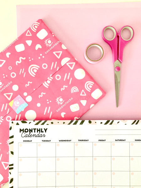 custom pink branded tissue paper with a pink, black and white monthly desk calendar and a pair of pink scissors