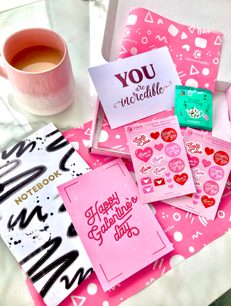 coconutacha patreon goodie box for valentines day featuring a grid, gold foiled notebook, valentines planner stickers, a pink foiled postcard, a galentines day greeting card and a herbal teabag.