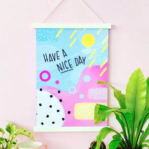 A brightly coloured art print placed on a pastel pink wall, surrounded by lush green plants in brightly coloured plant pots. The art print consists of abstract shapes and brightly coloured blues, pinks and yellows. There's a quote in a handwritten font saying 'have a nice day'.