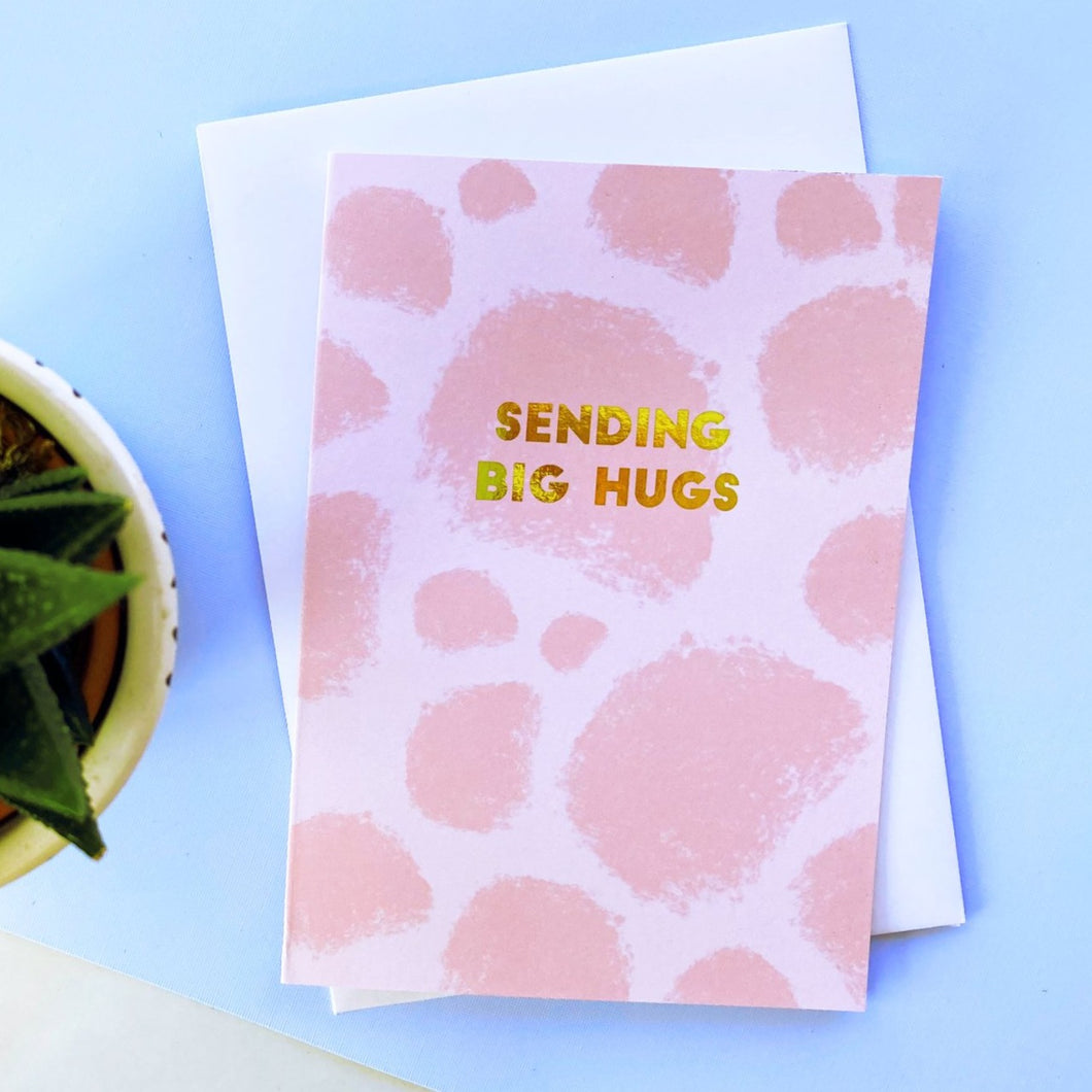 sending big hugs greeting card. pink with gold foil simple text.