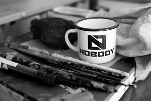 Nobody's coffee mug on a table with art brushes and clothes