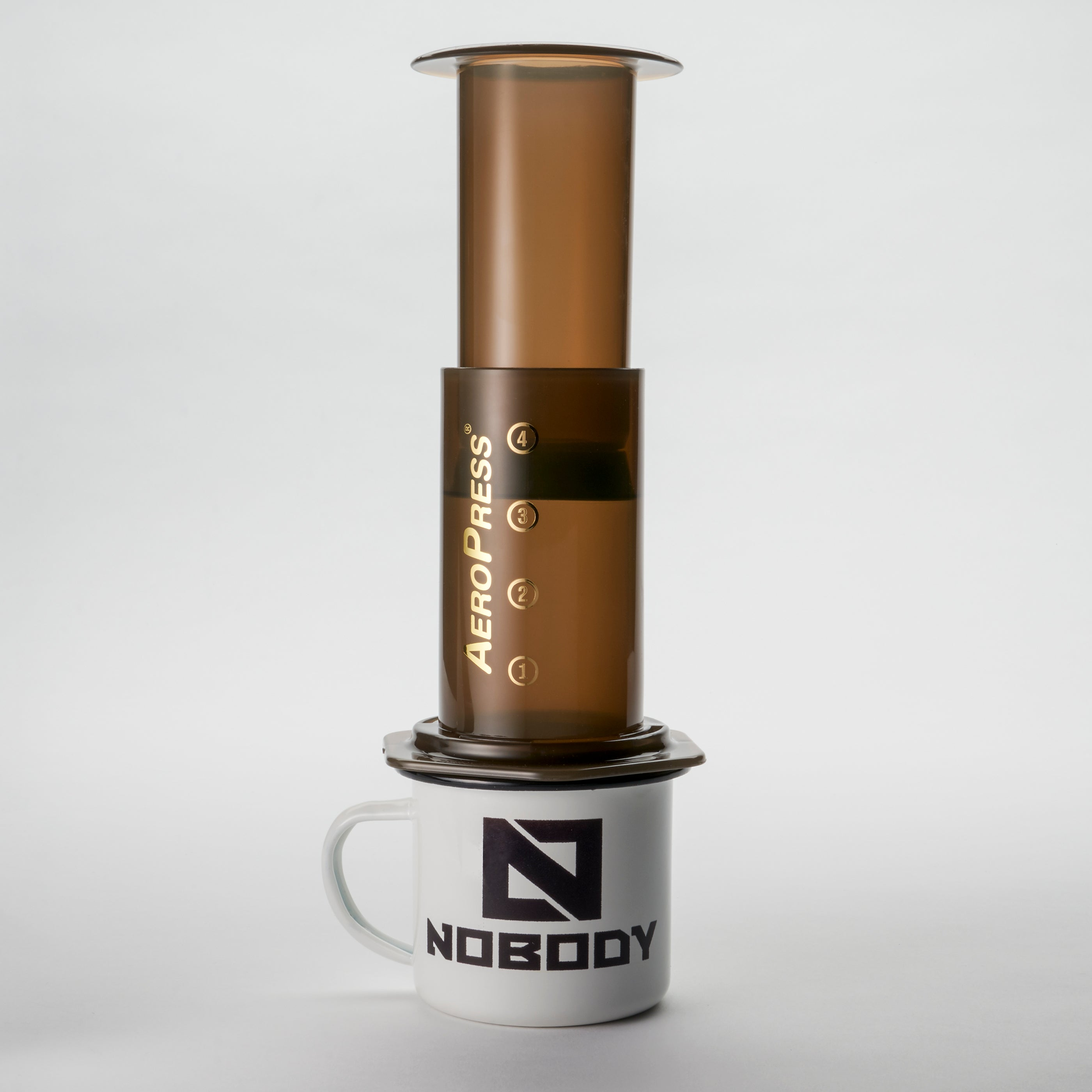 An aeropress coffee machine on a Nobody enamel mug.