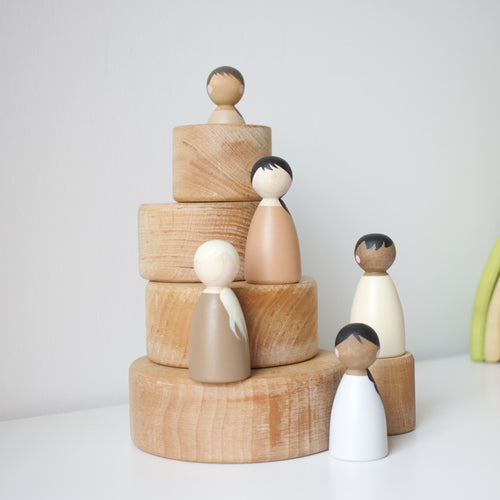 Lil peg dolls standing on top of grimm's stacking bowls