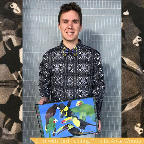 Model wears a black and white shirt with bird print and holds a painting of birds in his hands.