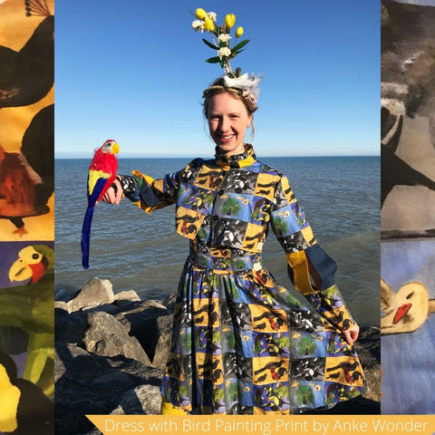 Model wearing a colorful bird print dress and holds a fake parrot in her hand.