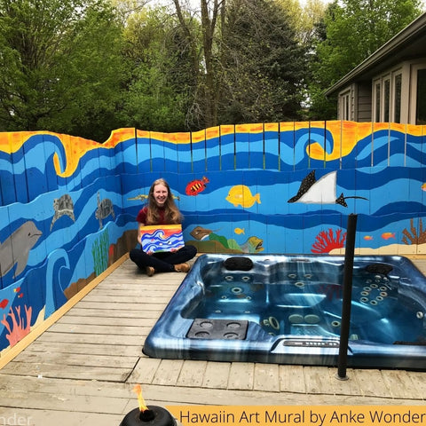 Mural Art of Sealife with artist Anke Wonder sitting in front of it with the sketch.
