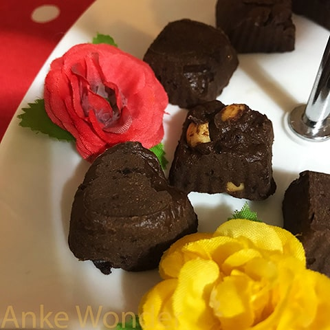 Chocolate Pralines with flower decoration on a white porcelain plate.