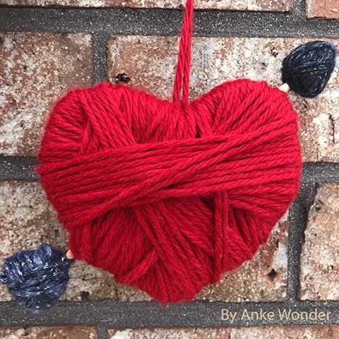 Heart with an arrow out of red and black yarn in front of a brick wall.