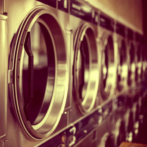 Several Washing Machines standing next to each other.