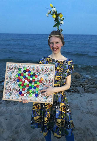 Wisconsin Bottle Cap Artwork made out of Bottle Caps with Lake Michigan in the background. The designer Anke Wonder holds the Bottle Cap Artwork.