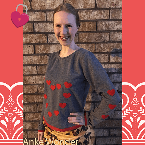 Woman standing in front of a brick wall while wearing a grey shirt with red heart applications.