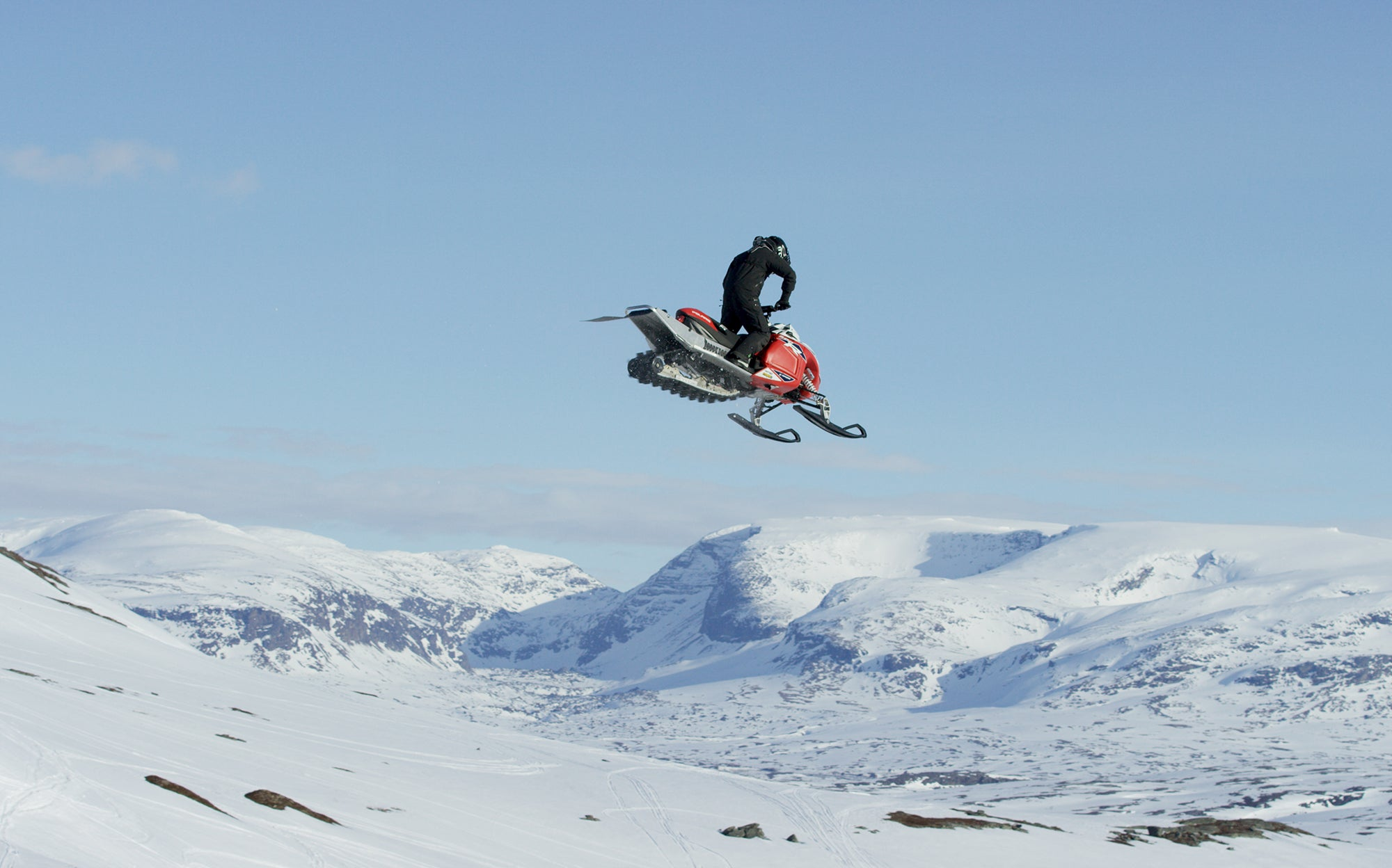 Sondre Zachariassen snowmobiling in the TOBE Vivid Mono Suit