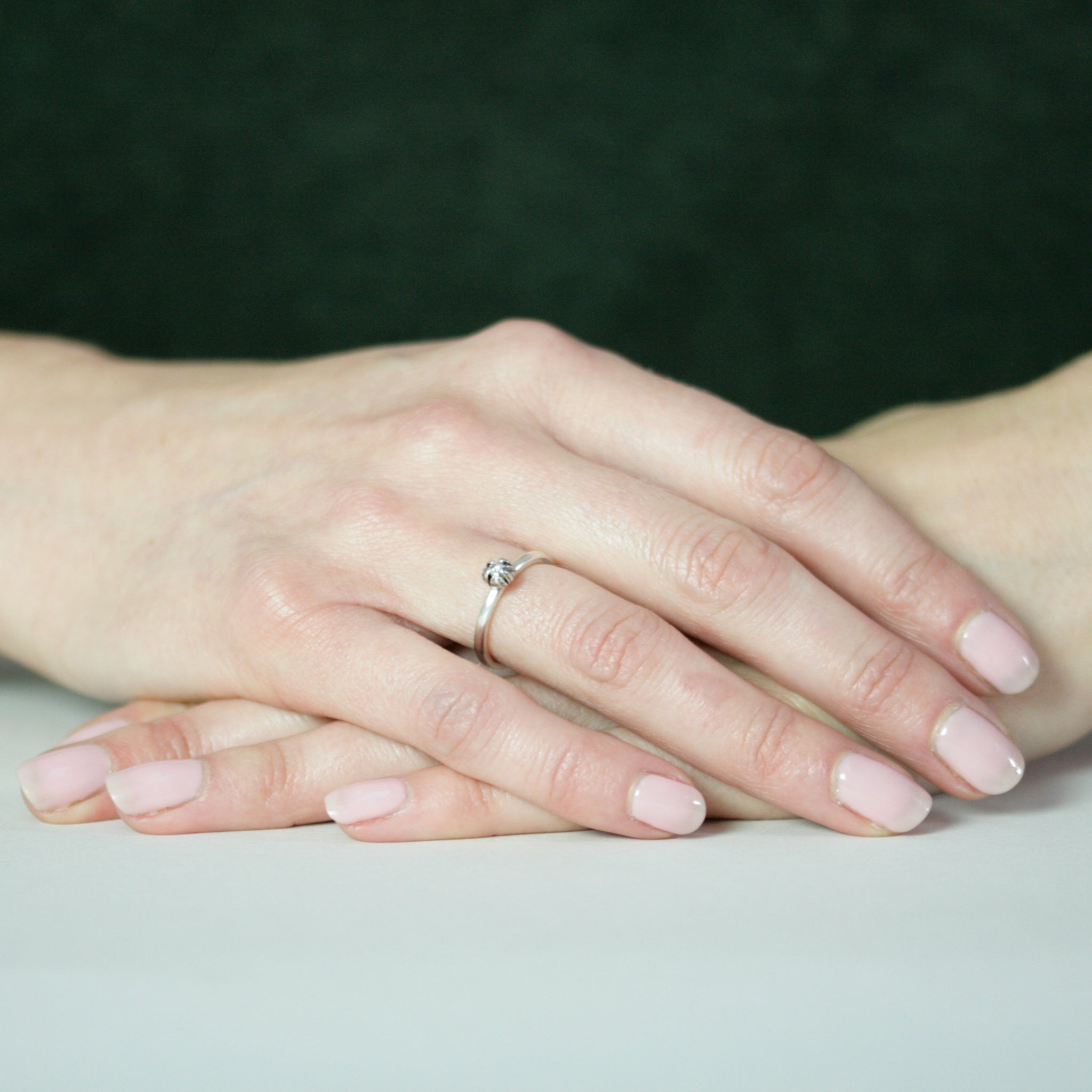 hands resting with silver bud diamond ring on finger