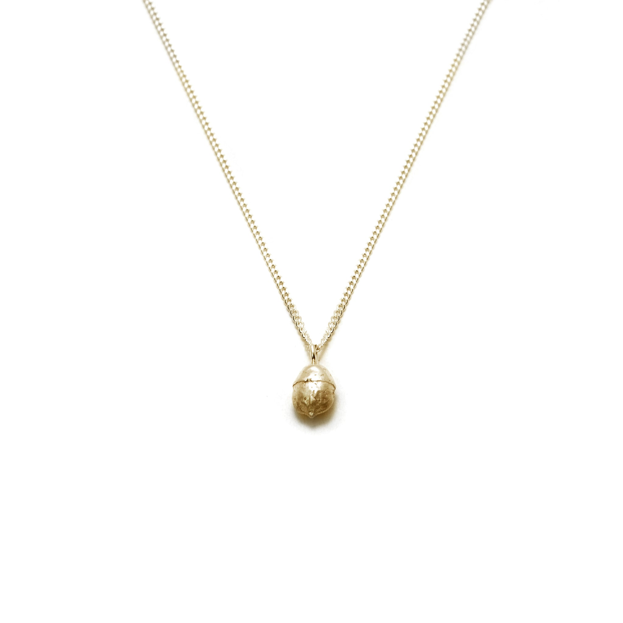 gold yew berry necklace on white background
