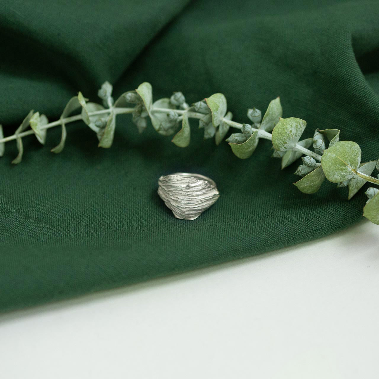 silver artichoke leaf ring on green cloth with dried flower