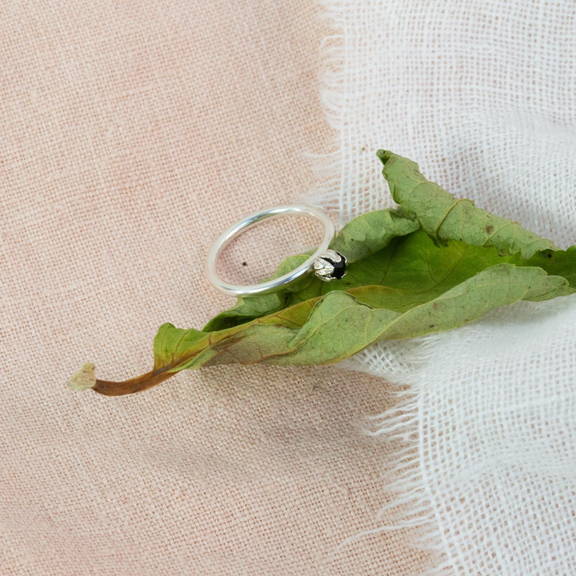 silver bud diamond ring restring on green leaf on cloth material